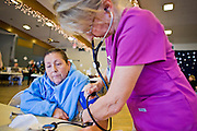 08 DECEMBER 2010 - PHOENIX, AZ: MARIA GARCIA (left) sees ELIZABETH OSBORN, a volunteer nurse, at a Mission of Mercy mobile clinic in Phoenix, AZ, Wednesday, Dec. 8. Mission of Mercy has been providing free medical help for people in the Phoenix area since 1997. In the last two years, as the Arizona economy continued its recessionary slide, patient load at the clinics has more than doubled. Mission of Mercy, which relies on voluntary medical help and financial donations, recently acquired another mobile clinic so they could expand their reach into suburban areas they previously had not served. Mission of Mercy has provided free medical help to more than 43,000 patients in the Phoenix area since 1997.   PHOTO BY JACK KURTZ