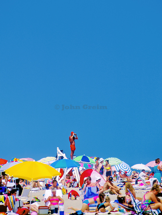 A lifeguard on a stand overlooking crowds at the beach. Cape Cod National Sea Shore, Massachusetts.