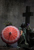 women praying to statue of the virgin mary with umbrella