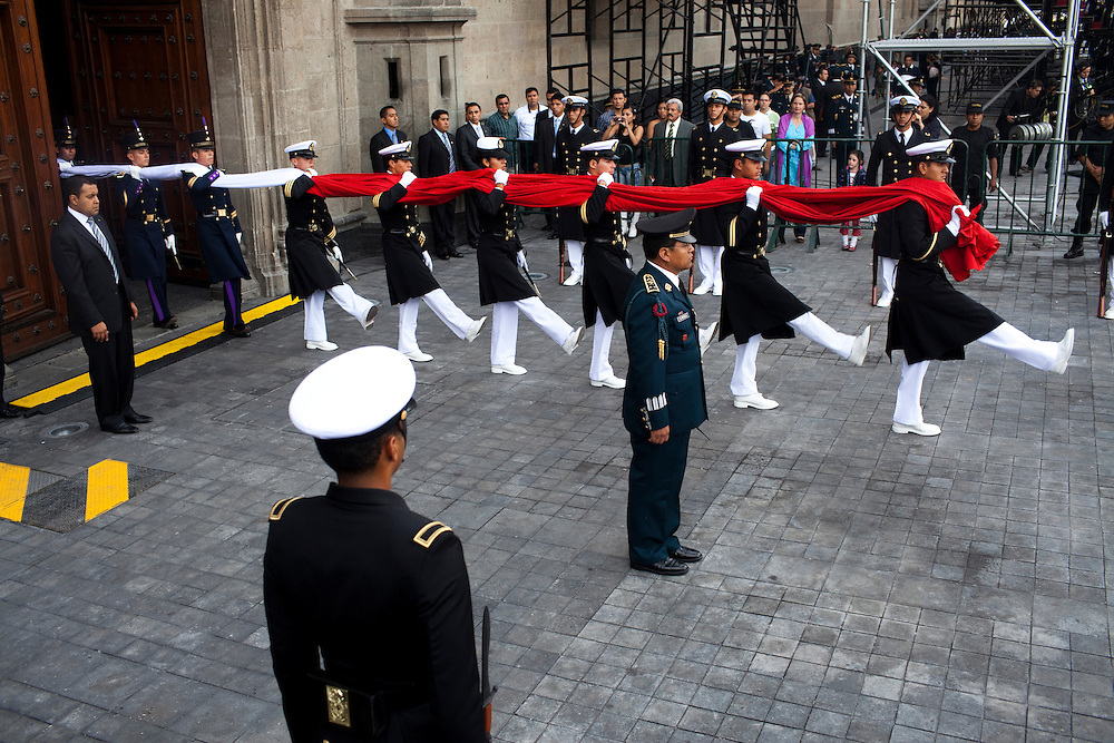 Officer carry the Mexican flag outside the presidential palace just before a parade for Mexico's bicentennial celebration, in Mexico City to mark the 200th anniversary of the uprising against Spanish rule which eventually led to their declaration of independence in 1821.
