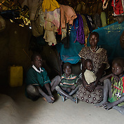 "Regina Libiriko with four of her six children in Kudo village in Eastern Equatoria, South Sudan on 8 August 2014. Due to a combination of drought in some parts of the country, the ravages of pests in others, and instability caused by war, many South Sudanese are facing acute food shortages and possibly famine. Regina says, ""I harvested 10 bundles of sorghum, and as I have six children, it will run out by the end of August. Then I will go to the bush and collect the leaves that we always eat, and prepare that for the children."" (Left to right: Matiya Adelino, Sebit Adelino, Al Libiriko Adelino, Regina Libiriko, and Peter Adelino.)"