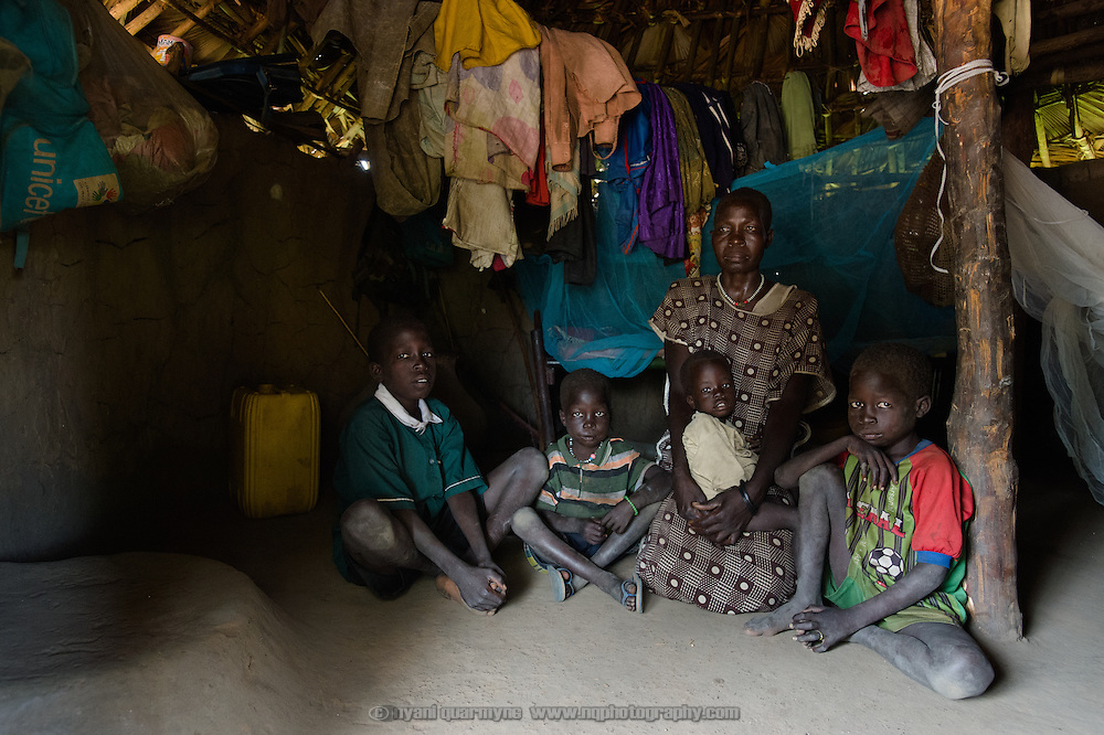 """Regina Libiriko with four of her six children in Kudo village in Eastern Equatoria, South Sudan on 8 August 2014. Due to a combination of drought in some parts of the country, the ravages of pests in others, and instability caused by war, many South Sudanese are facing acute food shortages and possibly famine. Regina says, """"I harvested 10 bundles of sorghum, and as I have six children, it will run out by the end of August. Then I will go to the bush and collect the leaves that we always eat, and prepare that for the children."""" (Left to right: Matiya Adelino, Sebit Adelino, Al Libiriko Adelino, Regina Libiriko, and Peter Adelino.)"""