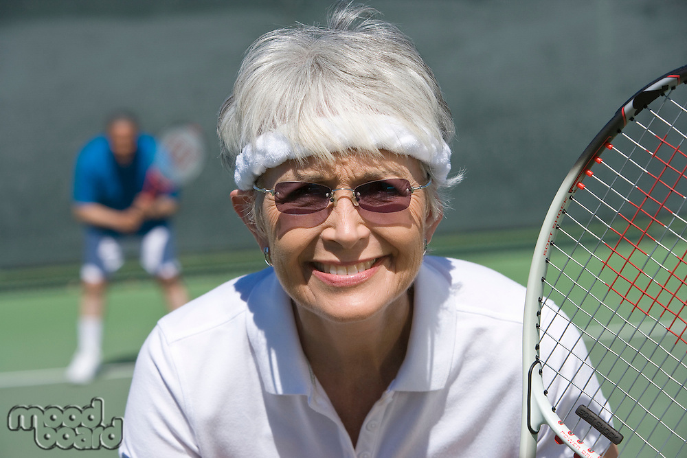 Senior woman playing tennis, portrait