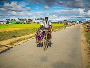 06 NOVEMBER 2014 - SITTWE, RAKHINE, MYANMAR: A Rohingya Muslim takes a fare down a road the connects Rohingya Muslim IDP camps near Sittwe. After sectarian violence devastated Rohingya communities and left hundreds of Rohingya dead in 2012, the government of Myanmar forced more than 140,000 Rohingya Muslims who used to live in and around Sittwe, Myanmar, into squalid Internal Displaced Persons camps. The government says the Rohingya are not Burmese citizens, that they are illegal immigrants from Bangladesh. The Bangladesh government says the Rohingya are Burmese and the Rohingya insist that they have lived in Burma for generations. The camps are about 20 minutes from Sittwe but the Rohingya who live in the camps are not allowed to leave without government permission. They are not allowed to work outside the camps, they are not allowed to go to Sittwe to use the hospital, go to school or do business. The camps have no electricity. Water is delivered through community wells. There are small schools funded by NOGs in the camps and a few private clinics but medical care is costly and not reliable.   PHOTO BY JACK KURTZ