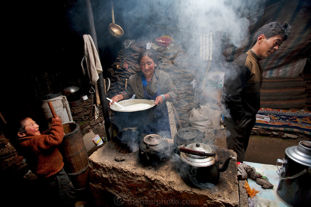 Six-year-old Nyima Dun Drup takes a turn at the butter churn as Phurba puts a pot of milk on the fire and Karsal talks to a neighbor at the Tibetan nomadic family's home in the Tibetan Plateau. (From the book What I Eat: Around the World in 80 Diets.)