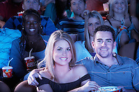 Young couple sitting arms around  Watching Movie in Theatre