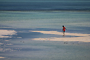 Local Child plays on the beach at low tide on the East Coast of Zanzibar