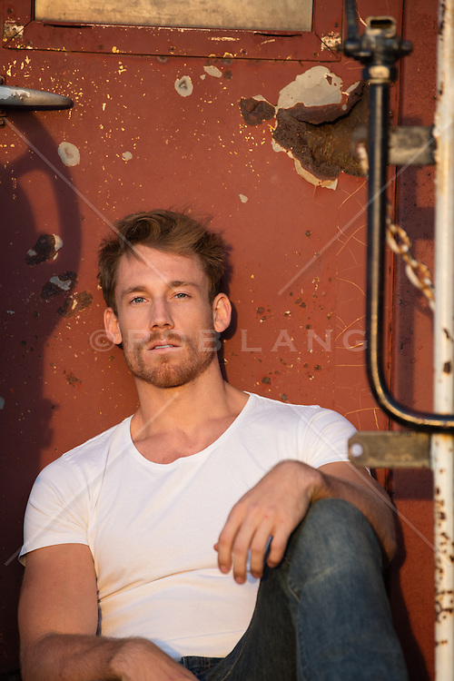portrait of an All American man leaning against a train at sunset