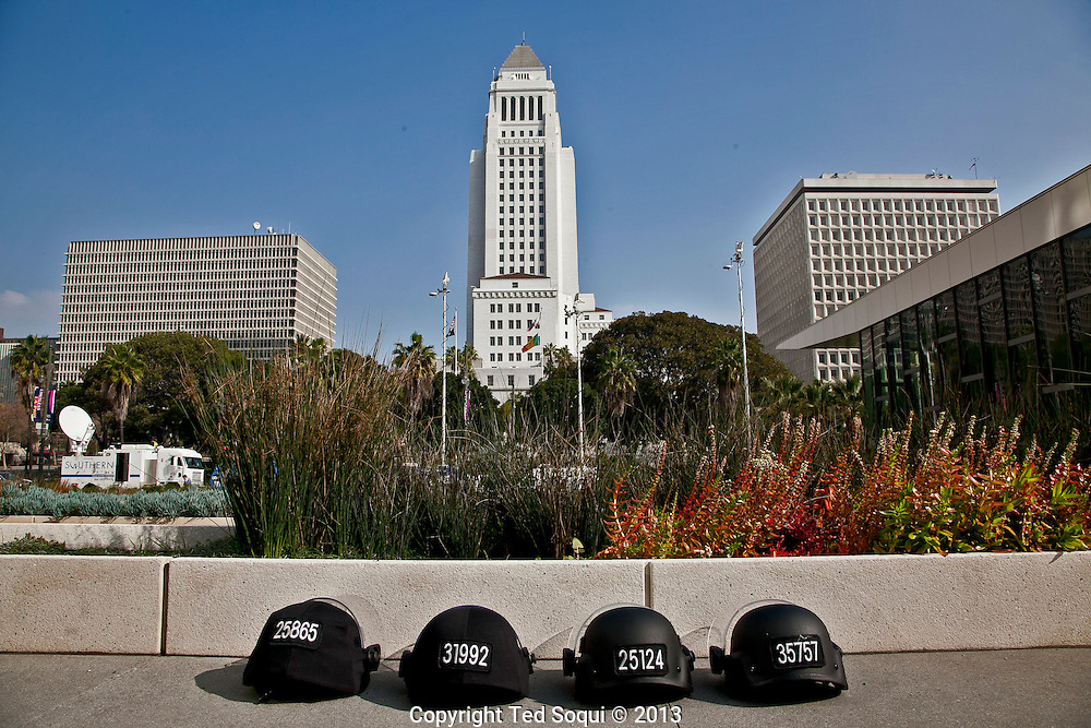 4 LAPD ballistic helmets lined up in front of the PAD building in downtown LA, LA City Hall is in the background.LAPD hold a press conference about ex LAPD officer turned fugitive, Christopher Jordan Dorner. Chief Beck spoke about the status of the search for Dorner.