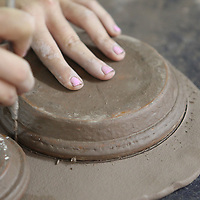 A mold is placed upside down on the newly rolled clay and then the excess clay is removed from around edges. The discarded clay is reused until it is to dry to work with.