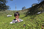 Kamon Nishino, aged 8, enjoys an ice-cream while playing in a park in Asakusa, with Skytree in the background. The summer of 2015 was one of the hottest on record at that time. Tokyo, Japan. Sunday July 19th 2015