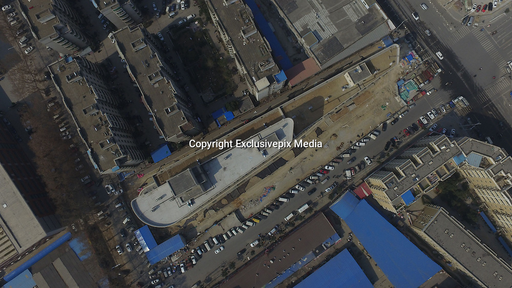 ZHENGZHOU, CHINA - FEBRUARY 15: <br /> <br /> Ship shaped Building Built In china<br /> <br /> Aerial view of a twelve-storey building, almost the same as a land cruiser, built on February 15, 2017 in Zhengzhou, Henan Province of China. The building is recognized as skinny and long measuring about 100 metres long, and the height of it is 35 metres. The newly-built building looking similar to a land cruiser will be put into use recently in Zhengzhou. <br /> ©Exclusivepix Media