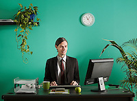 Young business man using computer at desk in office