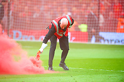 LONDON, ENGLAND - Sunday, May 12, 2013: No Pyro No Party. A Fulham steward removes a flare from the pitch as Liverpool supporters set off red smoke bombs during the Premiership match against Fulham at Craven Cottage. (Pic by David Rawcliffe/Propaganda)