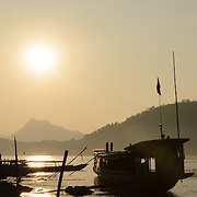 Boats and the shoreline silhouetted against the setting sun on the Mekong River in near Luang Prabang in central Laos.