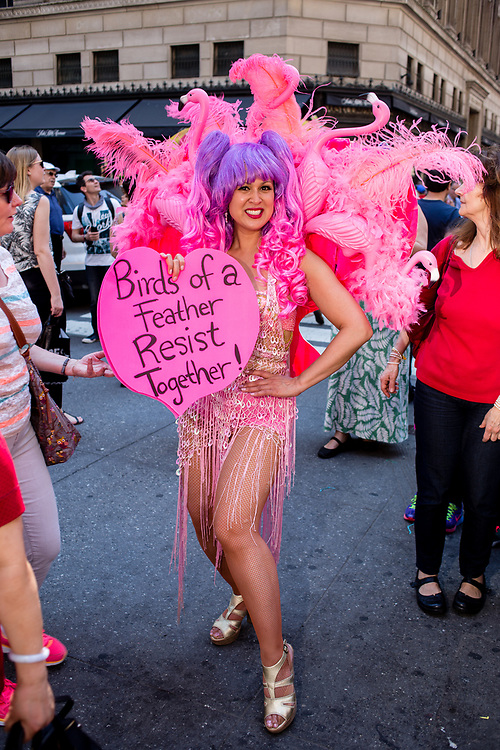 "New York, NY - April 16, 2017. Activist Marni Halasa wears a costume decorated by pink flamingoes and carries a sign reading ""Birds of a feather resist together""  at New York's annual Easter Bonnet Parade and Festival on Fifth Avenue."