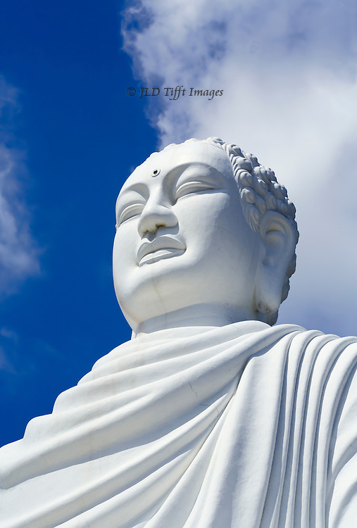 Oversize (24 meters high with base) seated Buddha statue at Long Son Pagoda, near Nha Trang, Vietnam, seen against a bright blue sky and shapely white clouds.  Statue was made in 1964-65 as a memorial to monks who immolated themselves in protest of the war between America and Vietnam. The pagoda on the hill below it dates from 1900, erected and still used as an educational institution.  This view looks up at the head and shoulders of the statue, against a bright blue sky and white clouds.  It exudes a feeling of serenity.