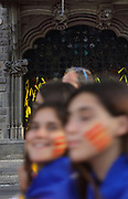 Festival goers with the catalan flag painted on their cheeks, marching to celebrate catalan nationalism, on Diada, or La Diada Nacional de Catalunya, Catalonia's National Day, on 11th September 2018, Barcelona, Catalonia, Spain. Behind are yellow ribbons tied to a gate, in support of activists jailed for their role in the push for catalan independence. 2018 saw the largest Diada march ever, organised by the Catalan National Assembly, with a million people taking to the streets, supporting secession and the reinstatement of the unrecognised Catalan Declaration of Independence after the referendum of 2017. Picture by Manuel Cohen