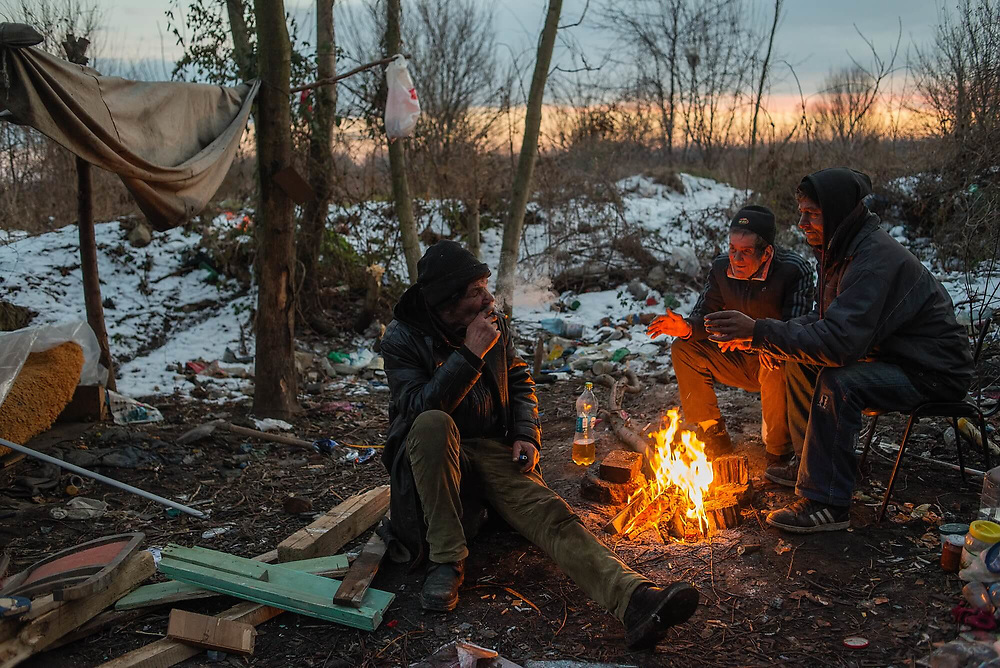 Three homeless men warming themselves beside a fire in the area of woodland where they have a shelter. In winter, once the temperature drops to freezing, they go to sleep in the sewage system.