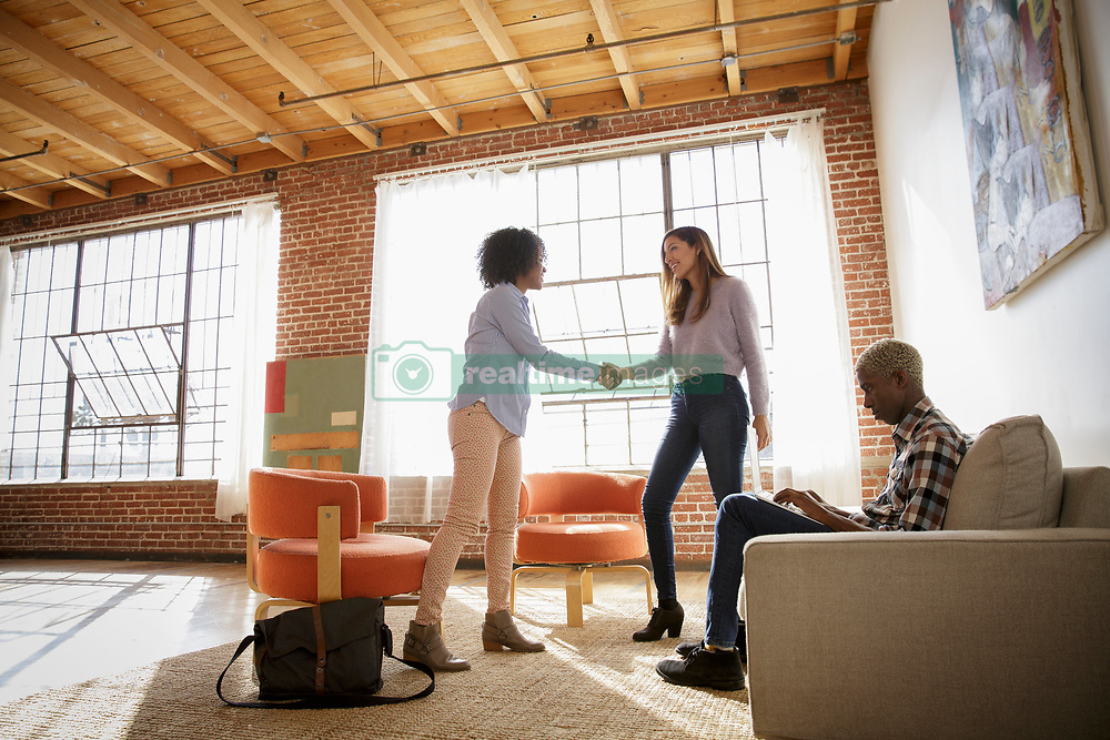 February 24, 2017 - Two women shaking hands in bare office, man sitting on sofa using laptop (Credit Image: © Image Source via ZUMA Press)