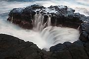 Pacific Ocean waves crash into a narrow inlet in an old lava flow near Princeville on the Hawaiian island of Kauai.