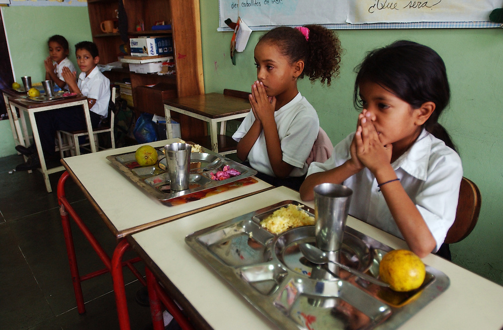 "Ana Cecilia Yamusa(right) , Dugleymis Martinez(next to Ana) and other students say grace in their 1st grade classroom at the Florencio Jimenez school.  The school is one of the new ""Bolivarian"" Schools which are part of President Chavez's Education Reform.  The new Bolivarian Schools keep students for an entire day, as opposed to a half day, feed the students lunch and offer programs like drama, art and music. While President Chavez touts his programs that benefit the poor, many point to a rising poverty rate and shrinking economy and claim the programs fail to substantially help.  ."