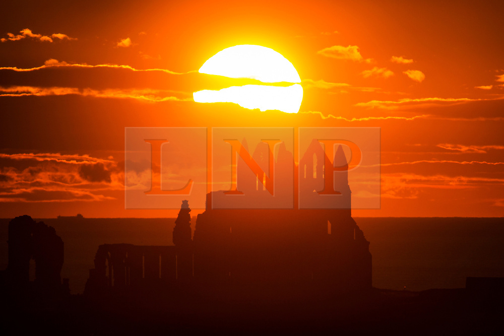 © Licensed to London News Pictures. 20/06/2019. Whitby, UK. The sun set's behind the Gothic ruins of Whitby Abbey on the Yorkshire coast last night. Photo credit: Andrew McCaren/LNP