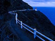A white fence winds along the cliffside trail to Makapuu Lighthouse on Oahu, Hawaii