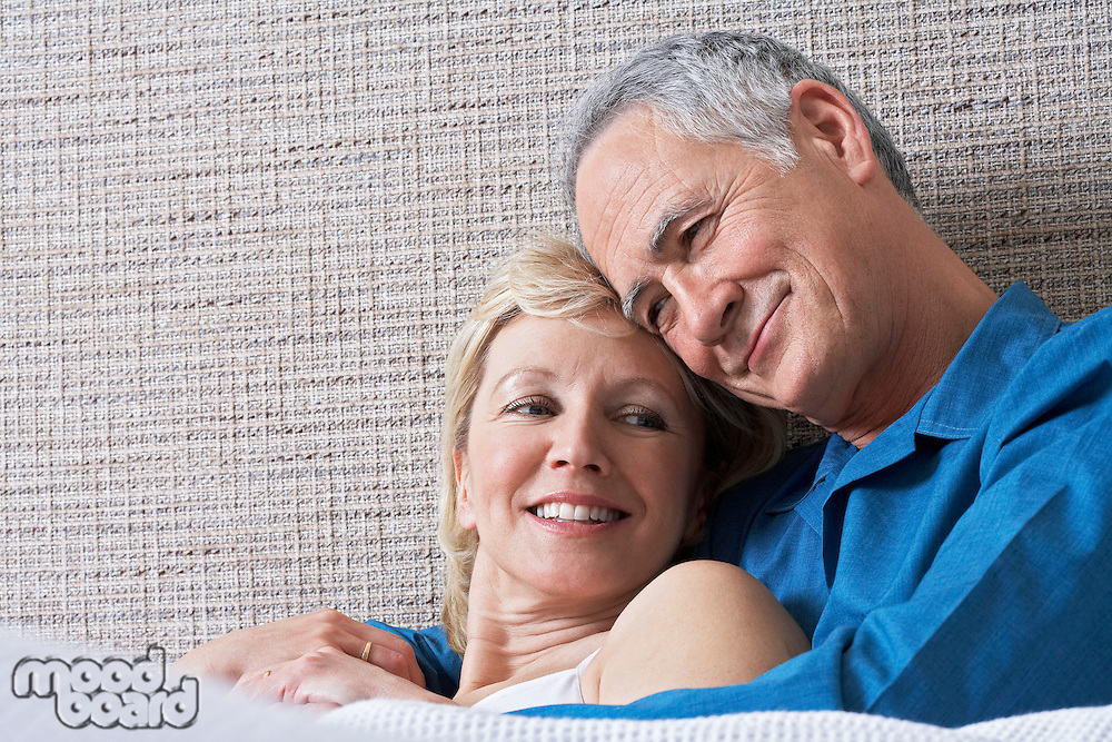 Middle-aged couple hugging in bed