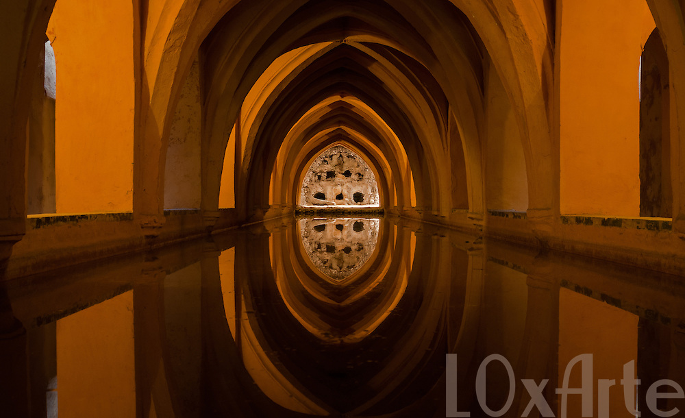 Light and arc reflection in a water reservoir within the Alcazar of Seville, Spain.