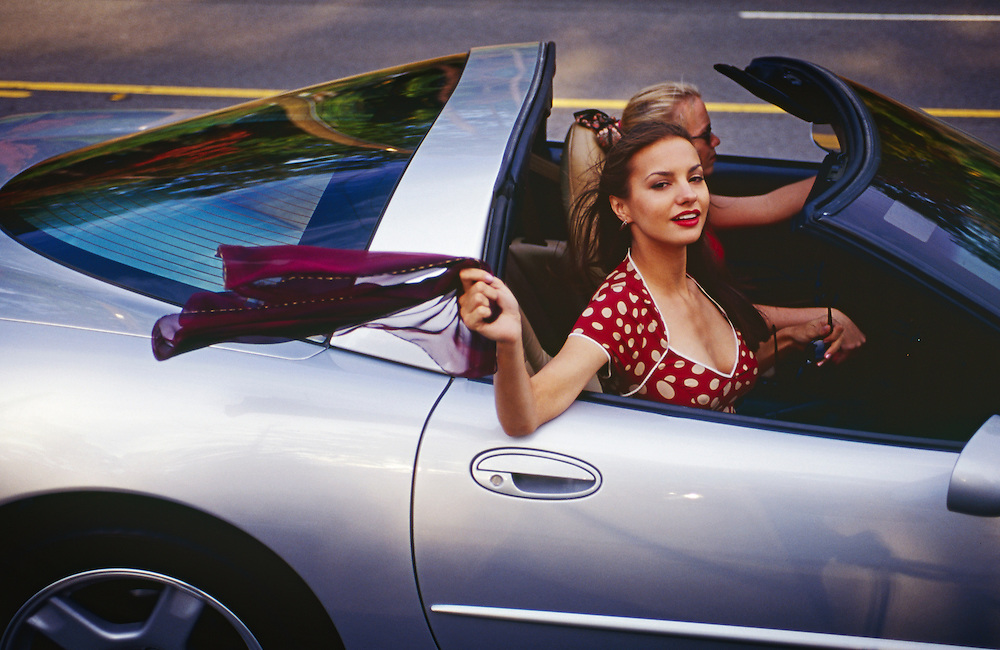 "A beautiful young woman in a red and white polka dot dress rides in a classic silver sports car. -- To determine pricing and license this image simply click ""Add To Cart"" below --"