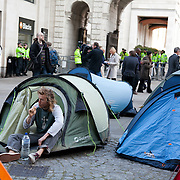A man is brushing his teeth in the door of his tent in the square with his back to the police protected Pator Noster Square.Day three of the occupation - and the first Monday. The Occupy London Stock Exchange movement was formed in London in solidarity with the US based Occupy Wall Street. The movements are a respons and in anger to what is seen by many as corporate greed and a failed banking system being bailed out by the public, - which in return are suffering austerity measures to make up for the billions of lost money. The movement occupied the St Paul's Square in the City of London Sat Oct 15 after it failed to secure and occupy Pator Noster Square and the Stock Exchnage itself.