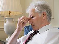 Business man sitting on sofa pinching bridge of nose close-up side view