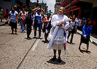 A woman dressed in white stands in a city street as citizens take to the streets as a day of protest in connection with Guatemala's President Alvaro Colom in Guatemala City May 17, 2009. . Thousands of protesters took to the streets of the capital  Sunday in two separated rival marches, one in support of the President and one denouncing President Alvaro Colom who was accused this week of murder, money laundering and having ties with narco-traffickers.(Darren Hauck)
