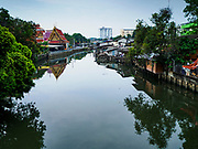 "22 MARCH 2018 - BANGKOK, THAILAND: Wat Lat Phrao (left) along Khlong Lat Phrao, the homes on the right side of the khlong (canal) are being demolished. Bangkok officials are evicting about 1,000 families who have set up homes along Khlong  Lat Phrao in Bangkok, the city says they are ""encroaching"" on the khlong. Although some of the families have been living along the khlong (Thai for ""canal"") for generations, they don't have title to the property, and the city considers them squatters. The city says the residents are being evicted so the city can build new embankments to control flooding. Most of the residents have agreed to leave, but negotiations over compensation are continuing for residents who can't afford to move.      PHOTO BY JACK KURTZ"