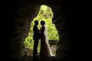 Bride and groom in silhouette standing on the stone bridge entrance to Watkins Glen State Park, Watkins Glen, NY
