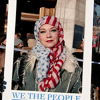 London UK. January 21st 2017.An estimated 100,000 protesters took part in a Women's March from the US Embassy in Grosvenor Square to Trafalgar Square as part of an international campaign on the first full day of Donald Trump's Presidency of the United States. A woman wears a US flag headscarf and holds an empty frame with the words 'We the people are greater than fear '...a reference to the posters designed by US artist Shepherd Fairley.