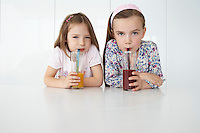 Two girls (7-9) sitting at table with orange and chocolate drinks portrait