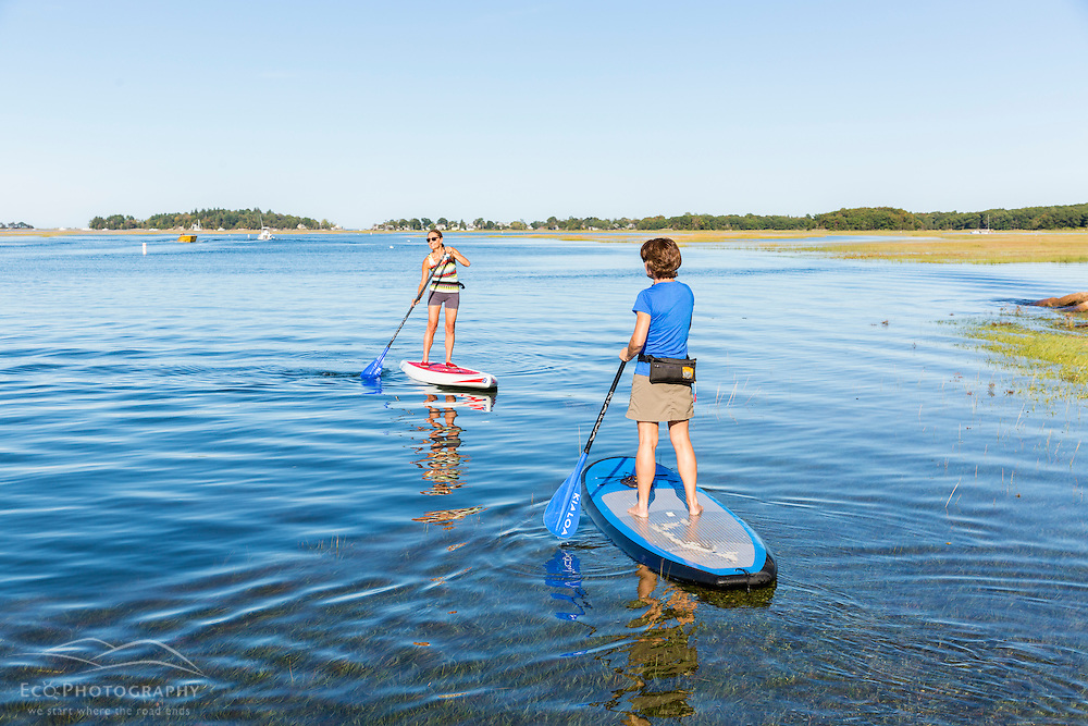 Two women stand up paddleboarding on the Essex River at the Cox Reservation in Essex, Massachusetts.