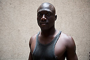 "Bass, Lamb's wrestler, age 24, 85kg, 1.81 mt. Member of Ecurie Fass from Parcelles, one of the most famous team in Senegal. Not yet in the professional category. Parcelles, Dakar, Senegal, on tuesday, April 07 2009.....""Lamb, the wolof word for fight, is a very popular type of African wrestling in Senegal. This ""lutte traditionelle"" has been transformed into a national cult, drawing massive following next only to football. Senegalese wrestlers are among the best-known national sports figures. The senegalese fight form allows blows with the hands (frappe), the only of the West African to do so. The lutteurs wrestle in a sandy arena and attempt to win by making their opponent's knees, shoulder, or back touch the sand. Matches are festive and lively occasions, with music, dancing, and praise singing for the athletes; the actual wrestling bouts, however, are often over within a few seconds. Presently, wrestling is arranged by business-promoters who offer prizes for the winners..The sport has produced its own legends, names such as Yékini, Tyson and Bombardier (stage names) are celebrities in Senegal. In particular Mohammed Ndao, aka Tyson,  the 34-year-old leader of the Boul Falé generation of Pikine, a Dakar suburb, did not only revolutionise the sport, by carving his own group identity, and upsetting the old guard, but he is also credited with insisting on commensurate remuneration for the wrestlers. A ""combat"" could start from 10 million CFA francs (about 20,000 US dollars) to 65 million CFA francs. (about 130,000 dollars). The phenomenal success is such that stakeholders are already talking about building a separate stadium for the sport in the country."""