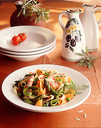 Pasta dish with shrimp and asparagus on tile with bowls and pitcher in background