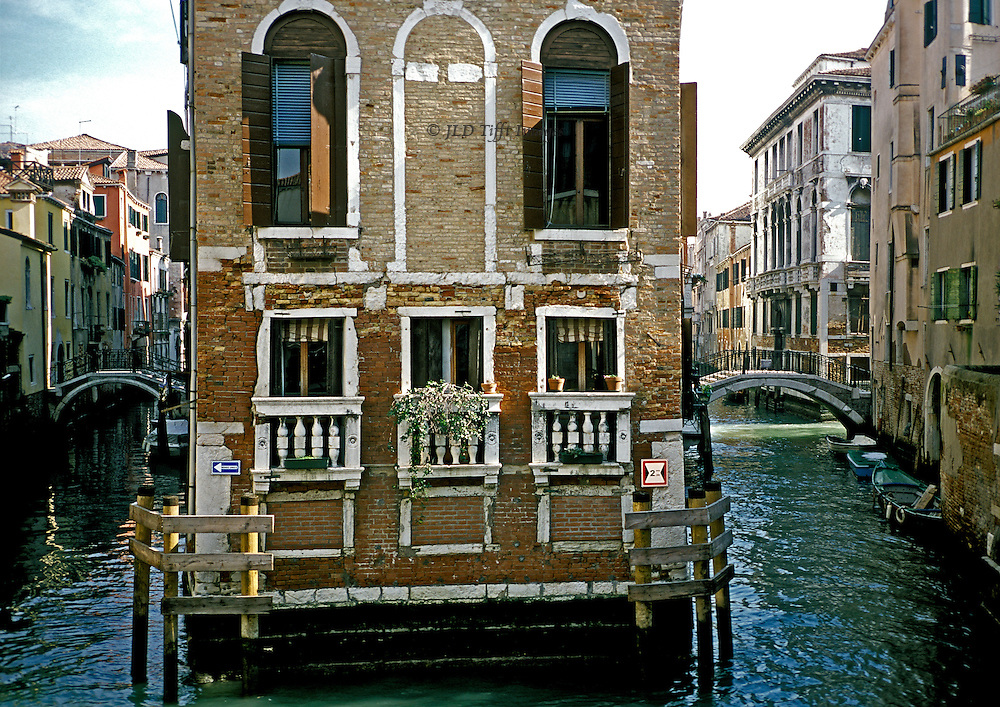 Private brick built stone trimmed palazzo in Venice with canal on three sides of it.  Balcony with potted plants, windows with wooden shutters and Venetian blinds, wooden bumpers at corners.  a hump backed bridge visible on each canal, lined with more palaces, homes, and apartments.  Three dinghies visible moored at right, a motor launch moored at the left.