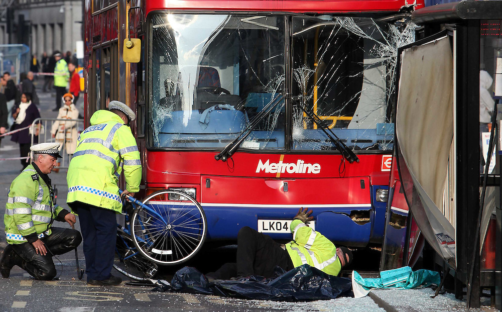 Police pull a fixed wheel bike from under a bus today on London's Oxford Street on 14.04.2010..A cyclist was left fighting for life after she was hit by a bus in Oxford Street in front of horrified onlookers...The 26-year-old woman received critical injuries in the collision with the 390 bus at around 1pm this afternoon near the junction with Tottenham Court Road.  14.04.2010.Ki Price +44(0)7940447610...