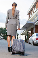 Back view of businesswoman walking suitcase on driveway