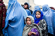 Kabul: Young girls wait in line with her mother at a UNHCR  distribution event at Tamir Mill Bus site...UNHCR distributes charcoal and NFI's to registered IDP's at one of Kabul's Informal Settlement Sites in the city centre...57 families eek out a living in a dilapidated warehouse building owned by the Ministry of Transportation. The site originally served as a storage facility for the national bus company...Tajik and Pashtun families live side by side without any major conflict. Over 70% of the families are returnees from the period 2002-2004 who are unable to achieve sustainable reintegration in their places of origin and subsequently drifted to Kabul City in search of work...There is a nearby school which is accessible to the children but the poor economic circumstances of the many families oblige them to send their children out to work. low levels of literacy, particularly amongst the women, limit their access to employment other than the lowest paid daily wage labor...Afghanistan. /UNHCR/Jason Tanner/February 2011