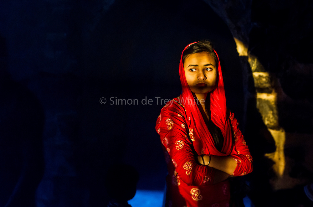 19th March 2015, New Delhi, India. A woman illuminated by a shaft of sunlight in the ruins of Feroz Shah Kotla in New Delhi, India on the 19th March 2015<br /> <br /> PHOTOGRAPH BY AND COPYRIGHT OF SIMON DE TREY-WHITE a photographer in delhi<br /> + 91 98103 99809. Email: simon@simondetreywhite.com<br /> <br /> People have been coming to Firoz Shah Kotla to leave written notes and offerings for Djinns in the hopes of getting wishes granted since the late 1970's. Jinn, jann or djinn are supernatural creatures in Islamic mythology as well as pre-Islamic Arabian mythology. They are mentioned frequently in the Quran  and other Islamic texts and inhabit an unseen world called Djinnestan. In Islamic theology jinn are said to be creatures with free will, made from smokeless fire by Allah as humans were made of clay, among other things. According to the Quran, jinn have free will, and Iblīs abused this freedom in front of Allah by refusing to bow to Adam when Allah ordered angels and jinn to do so. For disobeying Allah, Iblīs was expelled from Paradise and called &quot;Shayṭān&quot; (Satan).They are usually invisible to humans, but humans do appear clearly to jinn, as they can possess them. Like humans, jinn will also be judged on the Day of Judgment and will be sent to Paradise or Hell according to their deeds. Feroz Shah Tughlaq (r. 1351&ndash;88), the Sultan of Delhi, established the fortified city of Ferozabad in 1354, as the new capital of the Delhi Sultanate, and included in it the site of the present Feroz Shah Kotla. Kotla literally means fortress or citadel.