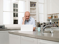 Middle-aged man using laptop in kitchen