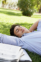 Mid-adult man lying on grass by newspaper close-up