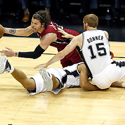 Jun 11, 2013; San Antonio, TX, USA; Miami Heat point guard Mario Chalmers (15) battles for control of a loose ball with San Antonio Spurs power forward Matt Bonner (15) and Tony Parker (9) in the first quarter during game three of the 2013 NBA Finals at the AT&T Center. Mandatory Credit: Derick E. Hingle-USA TODAY Sports