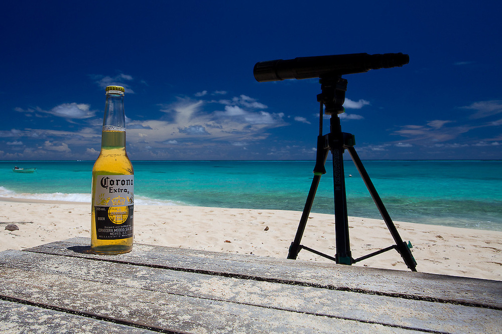 Close-up of Corona on Picnic Table on the Beach, with Telescope and White Sand, Aqua Water of Shore in Background, Fiji